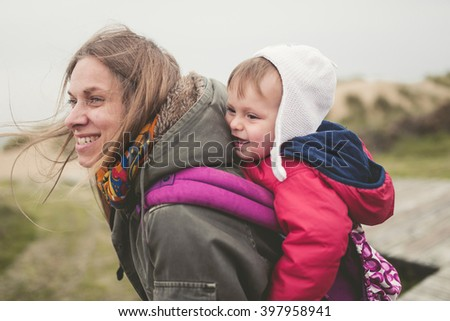 Mother carrying her child in a backpack outdoors in a cloudy day