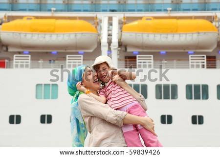 mother carrying her daughter and laughing, big cruise ship on background - stock photo
