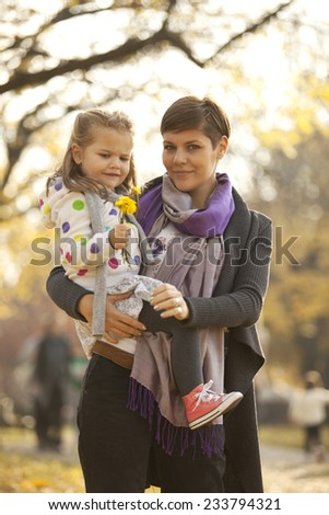 Mother Carrying Her Daughter In Arms With Flower In Hand Outdoor