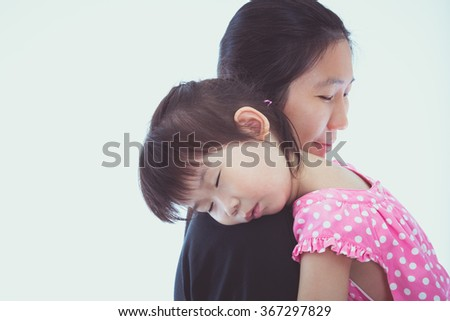 Mother carrying her daughter, little lovely asian girl sleeping on mom's shoulder, on white background. Studio shoot.  Mothers Day celebration. Vintage picture style. - stock photo