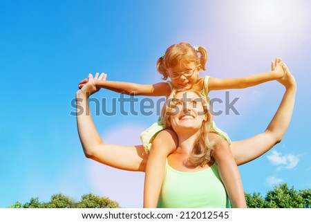 Mother carrying her daughter on shoulders outdoors, happy motherhood.Flare light - stock photo