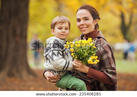 Mother carrying her son in one hand and flowers in the other hand - stock photo