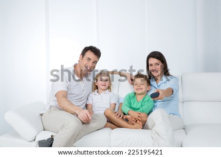 mother changes program on tv with remote control - stock photo