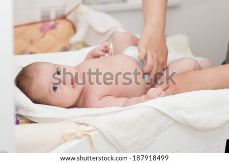 Mother changing a diaper of two month baby. - stock photo