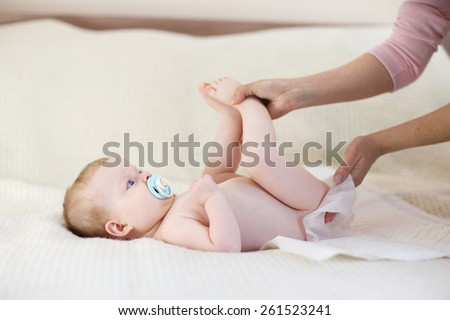 Mother changing a diaper to little baby girl - stock photo