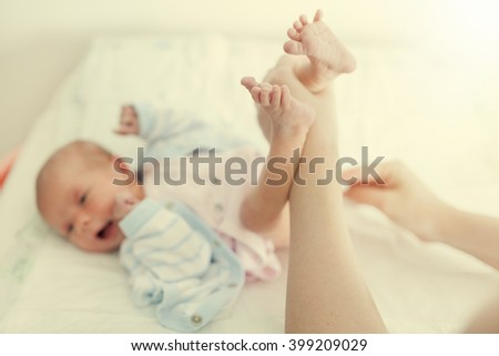 Mother changing cute baby girl's diaper. Post processed with vintage filter. - stock photo