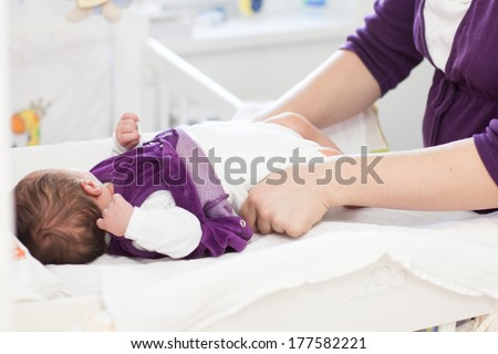 Mother changing diapers of newborn baby. - stock photo