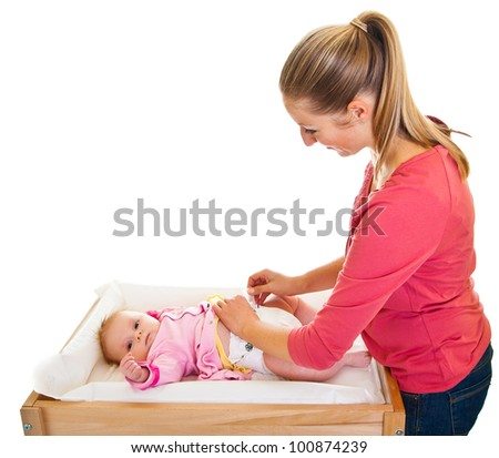 Mother changing little girl's diaper on nursery table