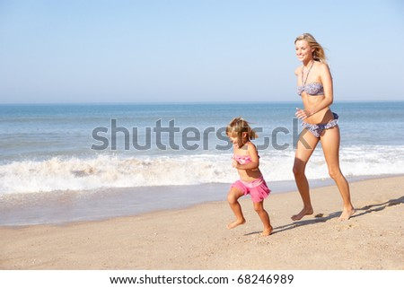 Mother chasing young girl on beach - stock photo