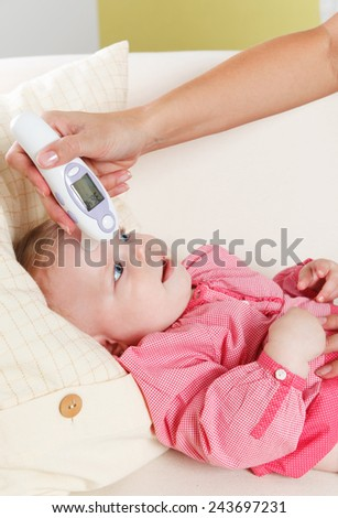 Mother checking baby girl's temperature - stock photo