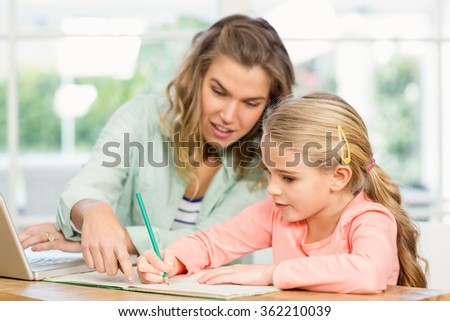 Mother checking her daughter's homework - stock photo