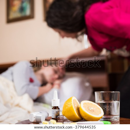 Mother checking temperature of sick daughter on a background. Medicines on a foreground - stock photo