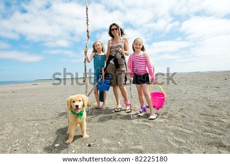 Mother, children and puppy at the beach - stock photo