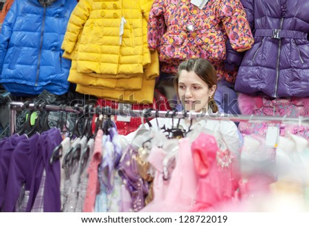 mother  chooses clothes for her child at children's wear store - stock photo