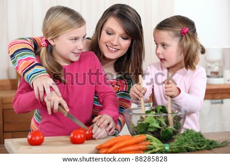 Mother chopping vegetables with two daughters