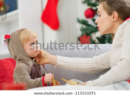 Mother cleaning eat smeared baby eating Christmas cookies - stock photo