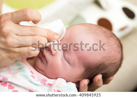 Mother cleaning eyes of a newborn baby with physiological solution on a cotton strip - stock photo