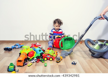 Mother cleaning the messy room full of toys. Close up on woman's hands cleaning with a vacuum cleaner. Upset kid playing with many toys on the floor - stock photo