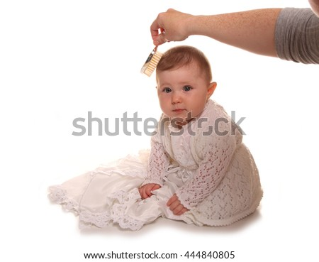 Mother combing babys girls hair before christening cutout - stock photo