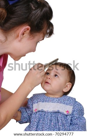 Mother combing one-year-old baby daughter's hair, isolated on pure white background - stock photo