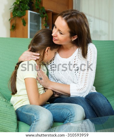 Mother comforting crying  daughter at home  - stock photo