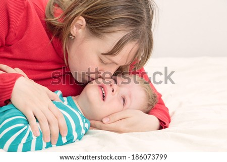 Mother comforting her crying little son - parenthood concept - stock photo