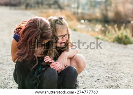 Mother consoling her hurt daughter at a park in Reno, Nevada, USA. - stock photo