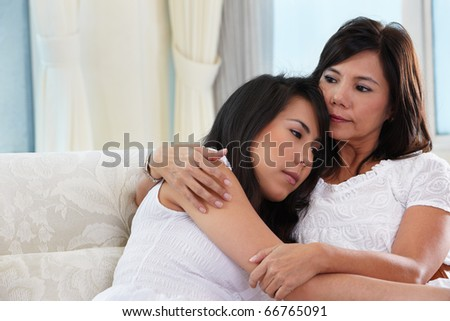 Mother consoling her sad daughter who has problem