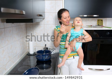 mother cook food in the kitchen and feed the baby - stock photo