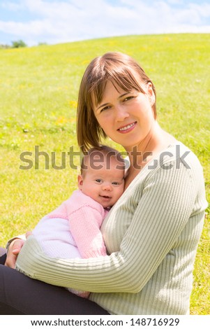 Mother cuddles her baby daughter sitting on a grass on a hill - stock photo