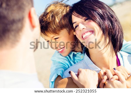 mother cuddles her son while father watches them moved - stock photo