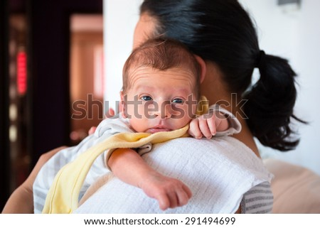 Mother cuddling her baby boy on arm - stock photo