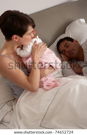 Mother Cuddling Newborn Baby In Bed At Home - stock photo