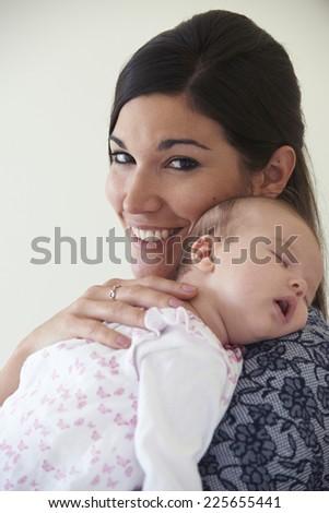 Mother Cuddling Sleeping Baby Daughter - stock photo