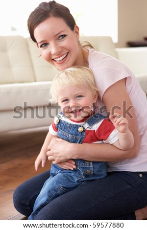 Mother Cuddling Son At Home - stock photo