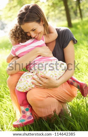 Mother Cuddling Young Daughter In Summer Field - stock photo