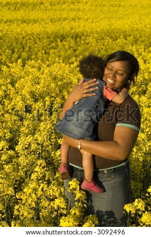 Mother, cute baby and lots of yellow flowers - stock photo