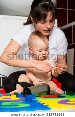 Mother cutting fingernails of her child while baby is playing with toys