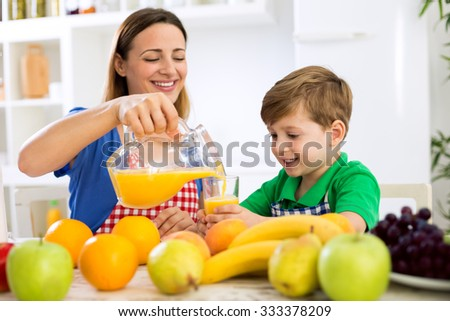 Mother cuttle orange juice to her child in kitchen - stock photo