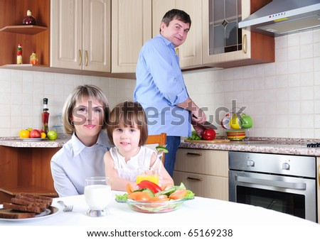 Mother, daughter and father has breakfast in the kitchen. father prepares a salad. Mom and daughter sit at the table. - stock photo