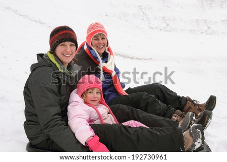 Mother, daughter, and granddaughter outdoors in the winter.  Sledding, sitting, and smiling at camera. - stock photo