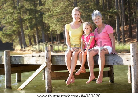 Mother,daughter and grandmother sitting by lake - stock photo