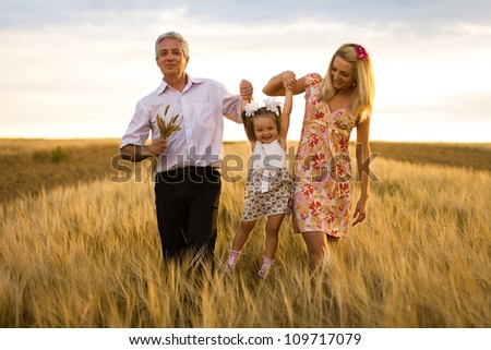 mother, daughter and grandpa with a bouquet of wheat in the sunlight having fun - stock photo