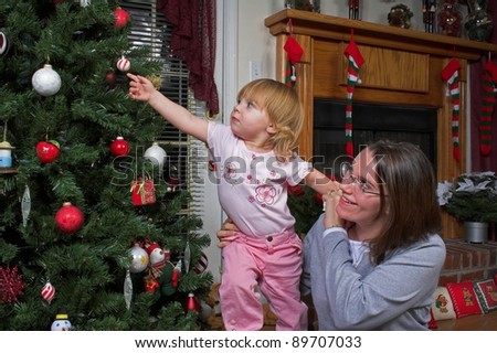 Mother & daughter exploring Christmas tree
