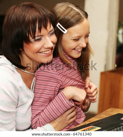 mother & daughter looking at compute.happy family. - stock photo