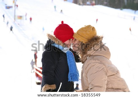 mother daughter noses together and warming in ski resort - stock photo