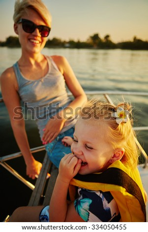 Mother, daughter on yacht or catamaran boat.  Concept of the family - stock photo