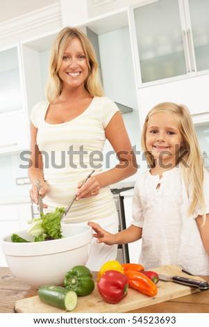 Mother & Daughter Preparing Salad In Modern Kitchen - stock photo