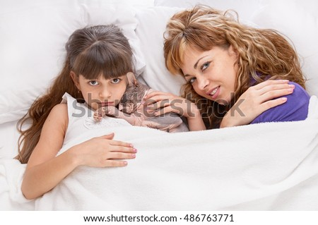 Mother daughter with cat on the bed