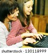 mother & daugther looking at compute.happy family. - stock photo